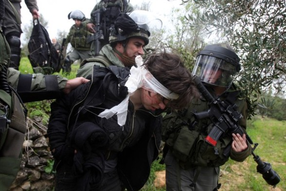 Israeli soldiers escort Naomi Laet, 22, an Israeli pro-Palestinian activist, after she was struck in the head with a rubber bullet during a protest in the West Bank village of Nabi Saleh, near Ramallah, on March 16, 2012 against land confiscation to build the Jewish settlement Hallamish nearby. AFP PHOTO/ABBAS MOMANI (Photo credit should read ABBAS MOMANI/AFP/Getty Images)