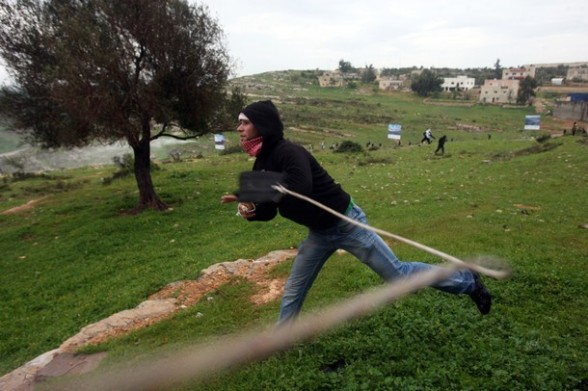 A Palestinian protester hurls a stone at Israeli soldiers during a protest in the West Bank village of Nabi Saleh, near Ramallah, on March 16, 2012 against the confiscation of Palestinian land to build the Jewish settlement Hallamish nearby. AFP PHOTO/ABBAS MOMANI (Photo credit should read ABBAS MOMANI/AFP/Getty Images)