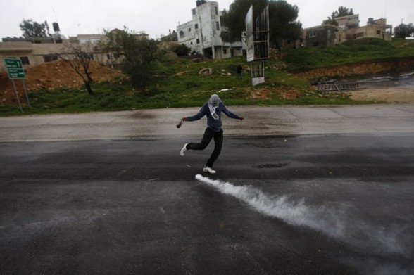 A Palestinian stone-thrower holds a sling as he kicks back a tear gas canister fired by Israeli soldiers during clashes at a weekly protest in the West Bank village of Nabi Saleh, near Ramallah March 16, 2012. REUTERS/Mohamad Torokman