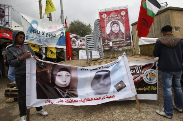 Palestinians hang up a banner depicting prisoner Hana Shalabi during a protest in front of her family house in the West Bank village of Birqin, near Jenin March 16, 2012. The deteriorating health of Shalabi, the Palestinian prisoner on hunger strike for the past month, is focusing international attention on Israel's decades-old use of detention without trial. REUTERS/Abed Omar Qusini