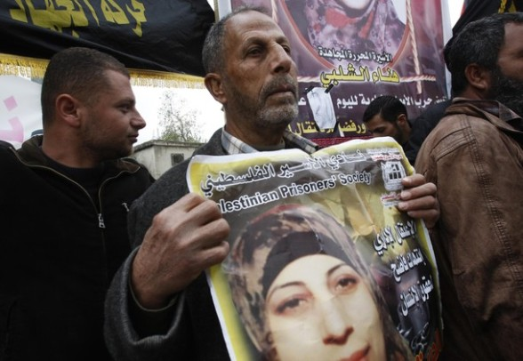 Yahya Shalabi (C), father of Palestinian prisoner Hana Shalabi, holds a poster of his daughter during a protest in front of their family house in the West Bank village of Birqin, near Jenin March 16, 2012. The deteriorating health of Shalabi, the Palestinian prisoner on hunger strike for the past month, is focusing international attention on Israel's decades-old use of detention without trial. REUTERS/Abed Omar Qusini