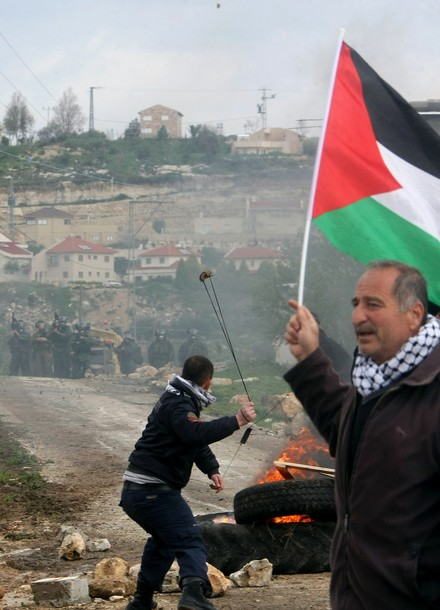 A Palestinian protester holds his national flag as another hurls a stone at Israeli soldiers during a demonstration against the expropriation of Palestinian land by Israel in the village of Kafr Qaddum, near Nablus in the occupied West Bank, on March 16, 2012. AFP PHOTO/JAAFAR ASHTIYEH