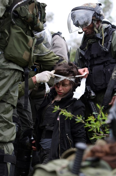 Israeli soldiers give first aid treatment to Naomi Laet, 22, an Israeli pro-Palestinian activist, after she was struck in the head with a rubber bullet during a protest in the West Bank village of Nabi Saleh, near Ramallah, on March 16, 2012 against land confiscation to build the Jewish settlement Hallamish nearby. AFP PHOTO/ABBAS MOMANI