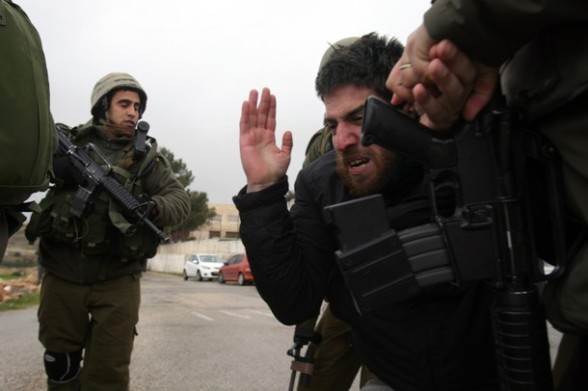 Israeli soldiers detain a foreign peace activist during a protest against Israel's controversial separation barrier in the village of Maasarah near the West Bank city of Bethlehem after the weekly Friday prayers on March 16, 2012. AFP PHOTO/MUSA AL SHAER