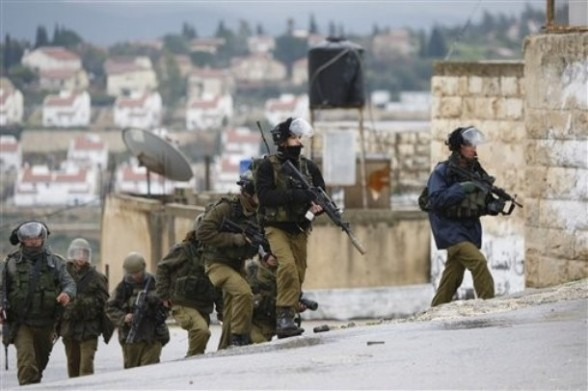 Israeli border police run towards Palestinian demonstrators during demonstration against the expansion of the nearby Jewish settlement of Halamish in the West Bank village of Nabi Saleh near Ramallah, Friday, March 16, 2012. (AP Photo/Majdi Mohammed)