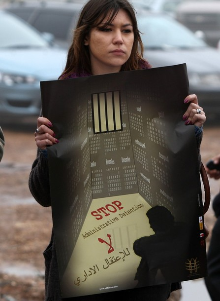 "A Palestinian protestor, holding a poster calling for the end of the administrative detention of female prisoner Hanaa al-Shalabi, demonstrates at the entrance to Ofer Prison near Ramallah in the Occupied West Bank to support Shalabi who was freed in a prisoner swap with Israel but was re-arrested on February 16 and has gone on hunger strike since. Shalabi ""is demanding the end of administrative detention (imprisonment without charge) and that the Israeli soldiers who beat her up and undressed her to carry out a body search be put on trial,"" her lawyer said. AFP PHOTO/ABBAS MOMANI"