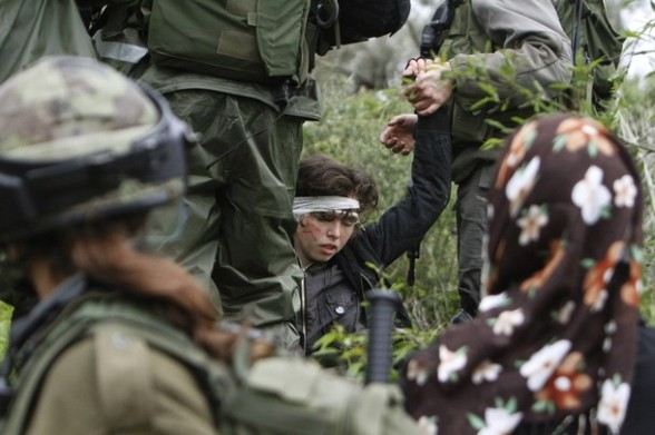 Israeli soldiers stand over Naomi Laet, 22, an Israeli pro-Palestinian activist, after she was struck in the head with a rubber bullet during a protest in the West Bank village of Nabi Saleh, near Ramallah, on March 16, 2012 against land confiscation to build the Jewish settlement Hallamish nearby. AFP PHOTO/ABBAS MOMANI