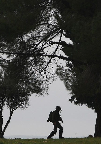 An Israeli soldier marches during a protest by Palestinian and foreign activists in the West Bank village of Nabi Saleh, near Ramallah, on March 16, 2012 against Palestinian land confiscation to build the Jewish settlement Hallamish nearby. AFP PHOTO/ABBAS MOMANI