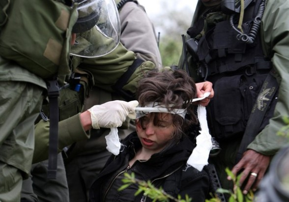 Israeli soldiers give first aid treatment to Naomi Laet, 22, an Israeli pro-Palestinian activist, after she was struck in the head with a rubber bullet during a protest in the West Bank village of Nabi Saleh, near Ramallah, on March 16, 2012 against land confiscation to build Jewish settlements nearby. AFP PHOTO/ABBAS MOMANI