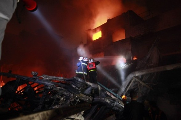 Palestinian fire fighters work to extinguish a fire at a building following an Israeli air strike in Gaza City March 14, 2012. A truce between Israel and militant groups in the Gaza Strip is tested with a bout of further rocket fire from Palestinian militants being met with Israeli air strikes. REUTERS/Suhaib Salem