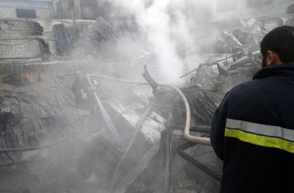 Palestinian firemen extinguish a fire at a building on March 14, 2012, after an Israeli air strike on Gaza City. Israel and militants in Gaza began observing an Egyptian-brokered truce on March 13, after four days of violence, which officials on both sides warned could flare up again. AFP PHOTO/MOHAMMED ABED