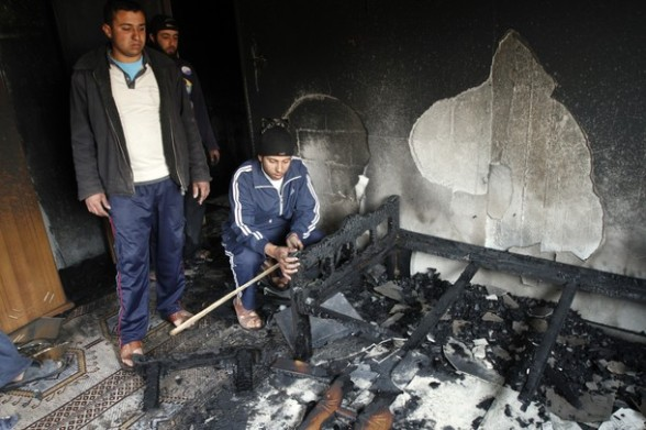 Palestinians inspect the damage in their house following a fire on March 14, 2012, that was induced by an Israeli air strike on Gaza City. Israel and militants in Gaza began observing an Egyptian-brokered truce on March 13, after four days of violence, which officials on both sides warned could flare up again. AFP PHOTO/MOHAMMED ABED
