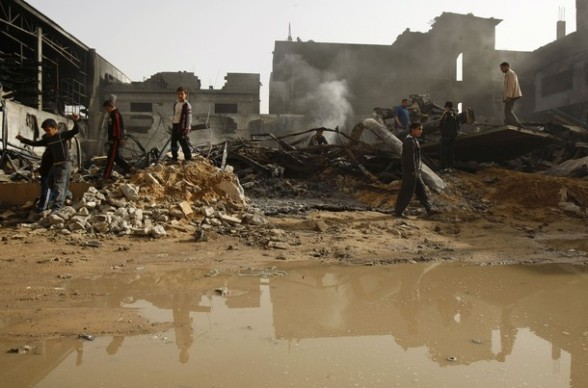 Palestinians walk atop the rubble of a building damaged after an Israeli air strike in Gaza City March 14, 2012. A Palestinian rocket hit the southern Israeli city of Netivot late on Tuesday, and the military responded shortly after with an air strike in Gaza city, but since then the frontier has been quiet. REUTERS/Ibraheem Abu Mustafa