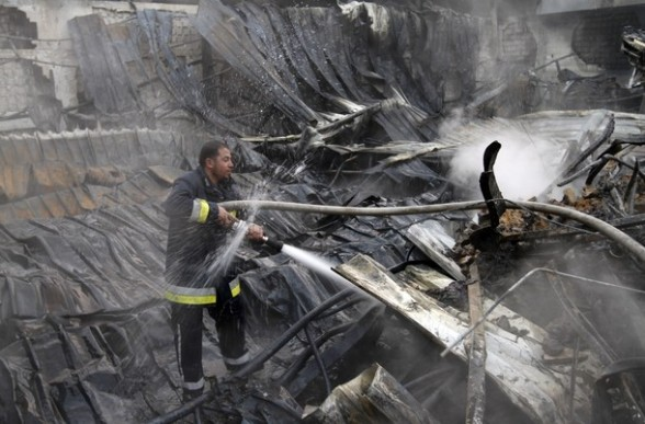 A Palestinian fireman extiguishes a fire at a building on March 14, 2012, after an Israeli air strike on Gaza City. Israel and militants in Gaza began observing an Egyptian-brokered truce on March 13, after four days of violence, which officials on both sides warned could flare up again. AFP PHOTO/MOHAMMED ABED