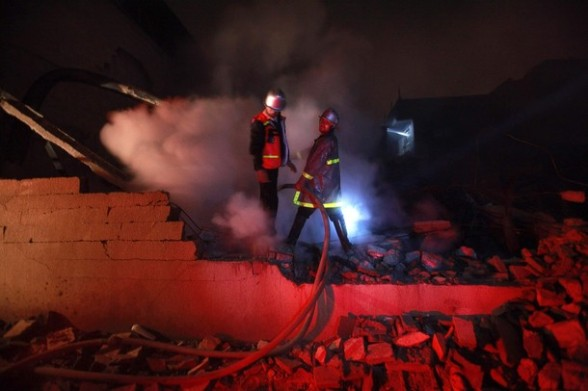 Palestinian fire fighters extinguish a fire at a building following an Israeli air strike in Gaza City March 14, 2012. A truce between Israel and militant groups in the Gaza Strip is tested with a bout of further rocket fire from Palestinian militants being met with Israeli air strikes. REUTERS/Suhaib Salem