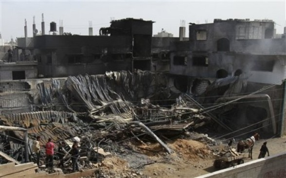 Palestinians inspect a warehouse which caught fire after an Israeli air strike near by in Gaza City, Wednesday, March 14, 2012. On Tuesday, Israel and Gaza militants agreed to a truce after four days of cross-border fighting, though there have been sporadic violations. (AP Photo/Adel Hana)