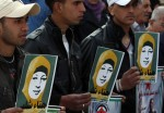 Palestinian protesters hold pictures of