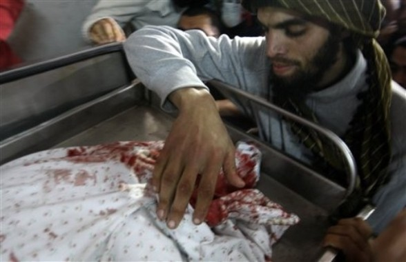 A Palestinian touches the body of  Zuhair al-Qaissi, a  commanderl of the armed wing of the Popular Resistance Committees (PRC) in Gaza City, Friday, March 9, 2012. An Israeli airstrike killed top Palestinian militant commander Zuhair al-Qaissi and a second militant in Gaza on Friday in the highest profile attack against the coastal strip in months. (AP photo/Hatem Moussa)