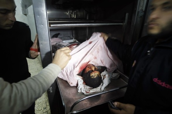 Palestinians look at the body of Mahmud