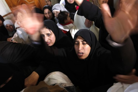 Palestinian women grieve as they watch the body of Palestinian youth Hashem Saed, 17-years-old, leave his home during his funeral in Gaza City on April 4, 2012, after he was shot overnight close along the border fence between the Gaza Strip and Israel by Israeli soldiers. AFP PHOTO/MOHAMMED ABED