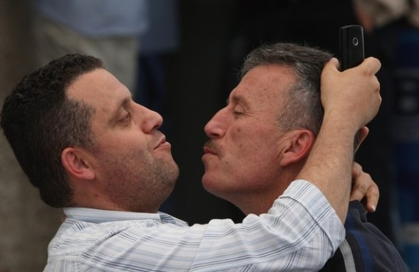 Palestinian activist Bassem Tamimi kisses a relative outside a hospital in Ramallah where his mother is being treated on April 25, 2012, after a military court released him on bail on April 24, ahead of the verdict in his trial on charges of organising popular protests. Tamimi was arrested on March 24, 2011 and accused of organising illegal demonstrations and incitement to stone-throwing in connection with a series of weekly demonstrations in the West Bank village of Nabi Saleh in protest at Jewish settlers taking over their land. AFP PHOTO / ABBAS MOMANI (Photo credit should read ABBAS MOMANI/AFP/Getty Images) 2012 AFP