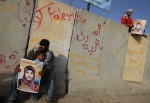 Palestinians hold posters of Hanaa Shalabi, a prisoner who spent 43 days on hunger strike, as they wait to greet her near the Erez border crossing between Israel and the northern Gaza Strip on April 1, 2012.  AFP PHOTO/MAHMUD HAMS
