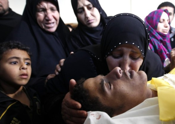 The sister of palestinian youth Hashem Saed, 17-years-old, kisses him farewell during his funeral in Gaza City on April 4, 2012, after he was shot overnight close along the border fence between the Gaza Strip and Israel by Israeli soldiers. AFP PHOTO/MOHAMMED ABED