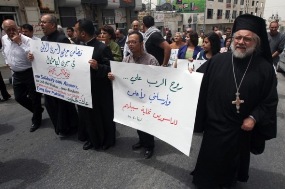 Palestinain priests and Christians protest in support of jailed Palestinians on hunger strike in Israeli prisons in the West Bank city of Ramallah on April 29, 2012. Over the past week, over 1,350 Palestinian prisoners have begun an open-ended hunger strike to protest against the conditions in which they are being held in Israeli jails. AFP PHOTO/ABBAS MOMANI