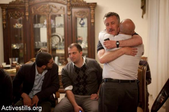 Bassem Tamimi hugs a friend, in the West Bank city of Ramallah after he was released from Ofer military jail, April 24, 2012.