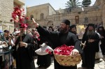 An Orthodox priest throws rose petals at the crowd as a procession arrives to the Church of the Holy Sepulchre in Jerusalem's Old City for Orthodox Easter mass April 15, 2012. REUTERS/Ammar Awad