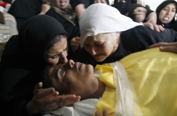 Female Palestinian relatives kiss farewell Hashem Saed, 17-years-old, during his funeral in Gaza City on April 4, 2012, after he was shot overnight close along the border fence between the Gaza Strip and Israel by Israeli soldiers. AFP PHOTO/MOHAMMED ABED