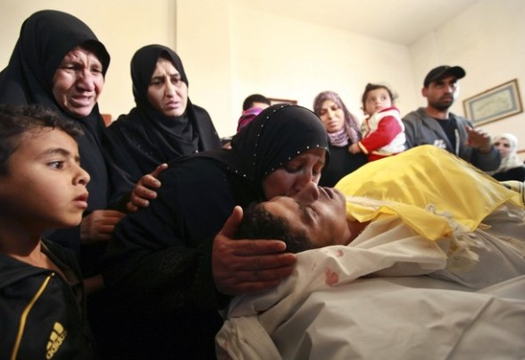 A Palestinian relative of Hisham Saad kisses his face during his funeral in the Gaza Strip April 4, 2012. According to Palestinian medical sources, Saad was killed by Israeli forces near the border between Israel and the east of Gaza City. REUTERS/Mohammed Salem