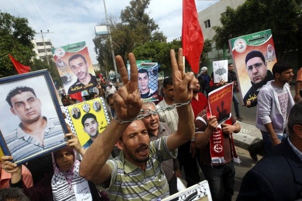Palestinians rally in Gaza City in support of more than a thousand prisoners who are on an open-ended hunger strike in Israeli jails on April 30, 2012. At least 1,350 Palestinian prisoners held in Israel are conducting a general hunger strike to protest their conditions. AFP PHOTO/MOHAMMED ABED