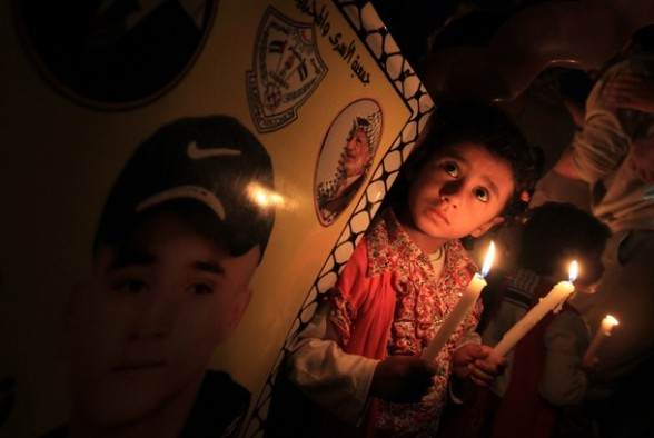 A Palestinian girl holds candles next to