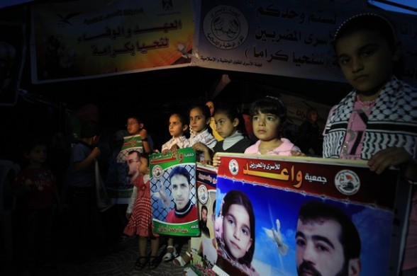 Palestinian children hold pictures of Palestinians being held in Israeli jails during an evening protest calling for their release in Gaza City on April 28, 2012. Some 1,600 Palestinian prisoners held in Israel are conducting a mass hunger strike to protest their conditions. AFP PHOTO/MAHMUD HAMS