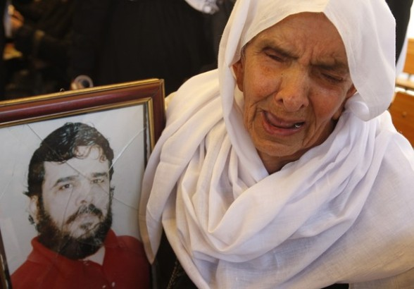 A Palestinian woman holding up a portrait of a jailed loved one takes part in a protest outside the Red Cross offices in Gaza City on April 23, 2012 calling for the released of Palestlinian prisoners held in Israel. At least 1,350 Palestinian prisoners being held in Israeli jails are observing an open-ended hunger strike, the Israeli Prisons Service said on April 22, after another 150 inmates began refusing food to protest the conditions in which they are being held.  AFP PHOTO/ MOHAMMED ABED
