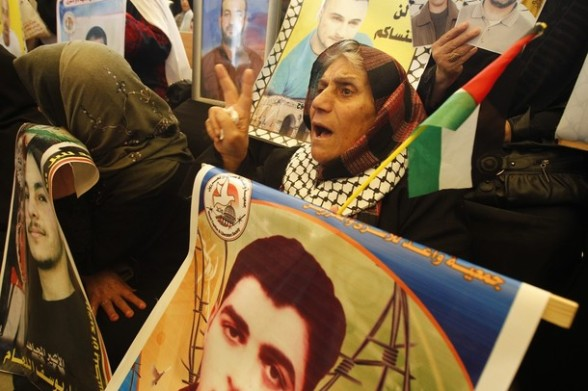 Palestinian women hold up portraits of incarcerated relatives during a protest calling for the release of Palestinian prisoners held in Israeli jails outside the Red Cross offices in Gaza City on April 23, 2012. At least 1,350 Palestinian prisoners being held in Israel are observing an open-ended hunger strike, the Israeli Prisons Service said on April 22, after another 150 inmates began refusing food to protest the conditions in which they are being held.  AFP PHOTO/ MOHAMMED ABED