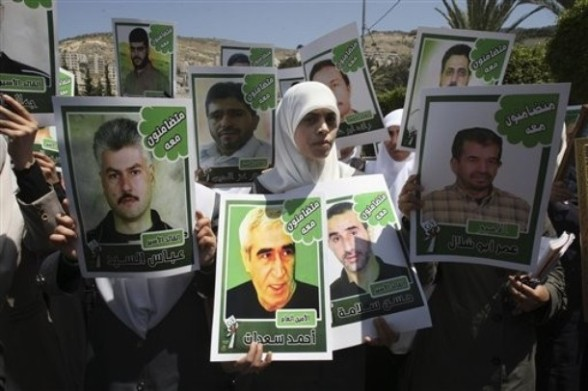 "Palestinians hold pictures of prisoners who were jailed in Israel during a demonstration calling for their release, in the West Bank city of Nablus,Thursday , April 26, 2012. Over 4,000 Palestinians are presently serving sentences in Israeli jails. Arabic writing on the posters read ""we support you."" (AP Photo/Nasser Ishtayeh)"