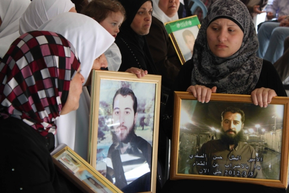 Women holding pictures of their loved ones, detained by Israel - Nablus Apr 26 2012 - Photo by WAFA