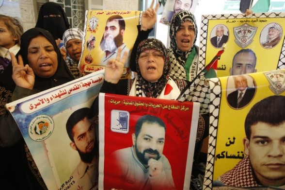 Palestinian women hold up portrait of incarcerated relatives during a protest calling for the release of Palestinian prisoners held in Israeli jails inside the grounds of the Red Cross office in Gaza City on April 16, 2012. Some 1,600 Palestinian prisoners held in Israel are due Sto begin a mass hunger strike on April 17 to protest their conditions, a Palestinian minister said.  AFP PHOTO/MOHAMMED ABED