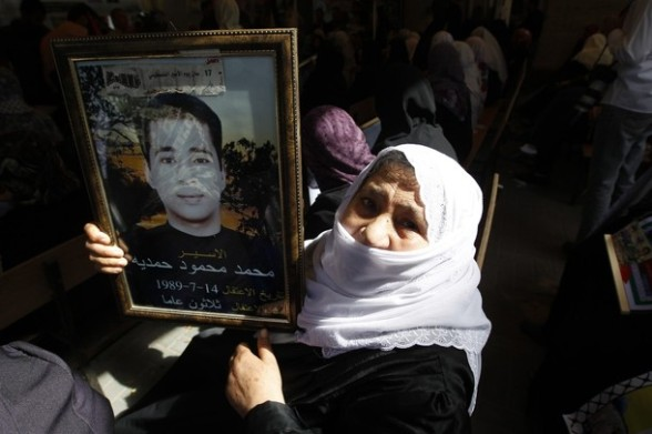 A Palestinian woman holds a portrait of her incarcerated son during protest calling for the release of Palestinian prisoners being held in Israeli jails inside the grounds of the Red Cross office in Gaza City on April 16, 2012. Some 1,600 Palestinian prisoners held in Israel are due Sto begin a mass hunger strike on April 17 to protest their conditions, a Palestinian minister said.  AFP PHOTO/MOHAMMED ABED