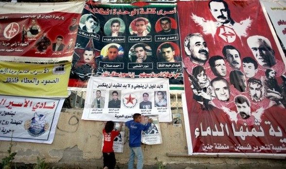 Palestinian children in the northern West Bank village of Araba, near Jenin, add pictures to a wall covered in posters of Palestinians held in Israeli jails on April 16, 2012, the eve of Prisoner's Day, which is an annual event during which people hold demonstrations and rallies of solidarity with the estimated 4,700 Palestinian inmates being held by Israel. Some 1,600 Palestinian prisoners held in Israeli jails are due to begin a mass hunger strike on April 17, to protest their conditions, a Palestinian minister said. AFP PHOTO / SAIF DAHLAH