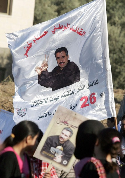 Palestinians hold a flag and placard picturing political prisoner, Hussam Khader, in the northern West Bank village of Araba, near Jenin on April 16, 2012 in preparation for of Prisoners' Day on April 17, which is an annual event during which people hold demonstrations and rallies of solidarity with the estimated 4,700 Palestinian inmates being held by Israel. Some 1,600 Palestinian prisoners held in Israeli jails are due to begin a mass hunger strike on April 17, to protest their conditions, a Palestinian minister said. AFP PHOTO / SAIF DAHLAH