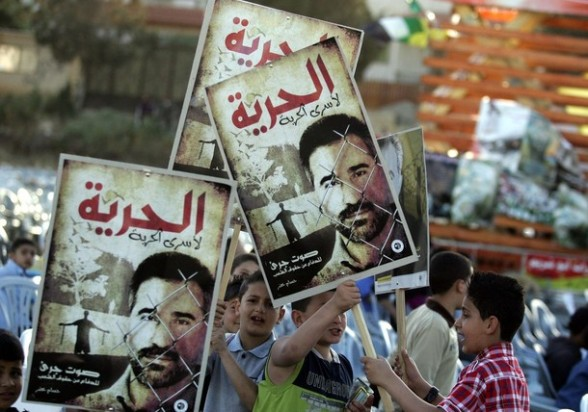 """Palestinian children hold placards of political prisoner Hussam Khader with text reading in Arabic: """"Free Prisoners"""" in the northern West Bank village of Araba, near Jenin on April 16, 2012 in preparation for of Prisoners' Day on April 17, which is an annual event during which people hold demonstrations and rallies of solidarity with the estimated 4,700 Palestinian inmates being held by Israel. Some 1,600 Palestinian prisoners held in Israeli jails are due to begin a mass hunger strike on Tuesday to protest their conditions, a Palestinian minister said. AFP PHOTO / SAIF DAHLAH"""