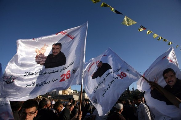 Palestinian hold flags picturing political prisoner, Hussam Khader, in the northern West Bank village of Araba, near Jenin on April 16, 2012 in preparation for of Prisoners' Day on April 17, which is an annual event during which people hold demonstrations and rallies of solidarity with the estimated 4,700 Palestinian inmates being held by Israel. Some 1,600 Palestinian prisoners held in Israeli jails are due to begin a mass hunger strike on April 17, to protest their conditions, a Palestinian minister said. AFP PHOTO / SAIF DAHLAH
