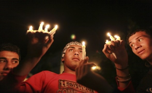 A protester holds candles during a rally to show solidarity with Palestinian prisoners inside Israeli jails, in front of the Red Cross headquarters in Gaza City April 16, 2012. Palestinian prisoners inside Israeli jails will begin a hunger strike on April 17, a Palestinian official said. REUTERS/Suhaib Salem