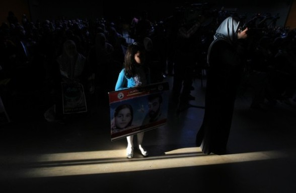 A Palestinian girl holds portrait of a prisoner as the audience watch a play depicting Palestinian prisoners in an Israeli jail in Gaza City on April 16, 2012 on the eve of Prisoners' Day, an annual event during which people hold demonstrations and rallies of solidarity with the estimated 4,700 Palestinian inmates being held by Israel. AFP PHOTO/MAHMUD HAMS