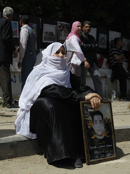 A Palestinian woman sits on the pavement holding a portrait of her incarcerated son during a protest calling for the release of Palestinian prisoners held in Israeli jails in front of the Red Cross offices in Gaza City on April 16, 2012. Some 1,600 Palestinian prisoners held in Israel are due Sto begin a mass hunger strike on April 17 to protest their conditions, a Palestinian minister said.  AFP PHOTO/MOHAMMED ABED