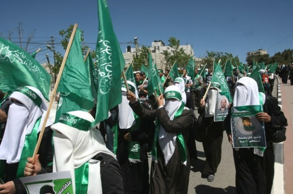 Female Palestinian Hebron University students, supportes of the Islamic Hamas movement, wave the movement's green flag as they rally to mark Prisoners' Day in the West Bank town of Hebron onApril 17,2012.  At least 1,200 Palestinian inmates of Israeli jails began an open-ended hunger strike as rallies across the Israeli occupied Palestinian territories marked Prisoners' Day.  AFP PHOTO / HAZEM BADER