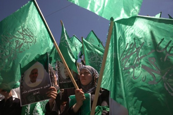 Palestinian Hebron University students, supporters of the Islamic Hamas movement, wave the movement's green flag as they rally to mark Prisoners' Day in the West Bank town of Hebron onApril 17,2012.  At least 1,200 Palestinian inmates of Israeli jails began an open-ended hunger strike as rallies across the Israeli occupied Palestinian territories marked Prisoners' Day.  AFP PHOTO / HAZEM BADER